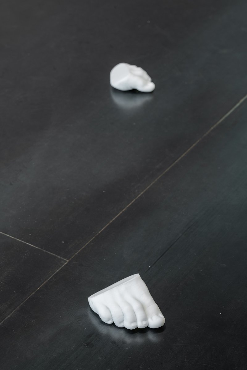 pair of partial feet, from toes to ball of foot, cast in white glass and placed on a dark floor